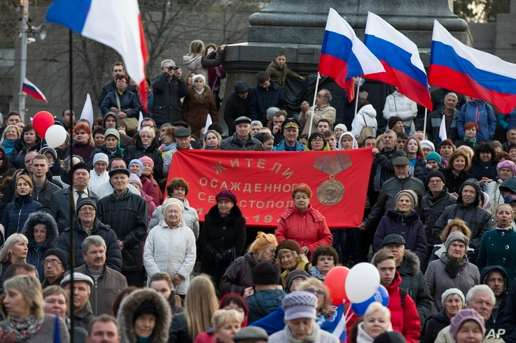 People gather with Russian national and Crimea flags, awaiting the start of a concert with Russian President Vladimir Putin addressing the crowd, in Sevastopol, Crimea, March 14, 2018.