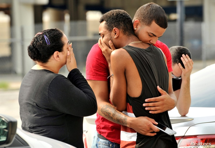Friends and family members embrace outside the Orlando Police Headquarters during the investigation of a shooting at the Pulse night club, in Orlando, Florida, June 12, 2016.