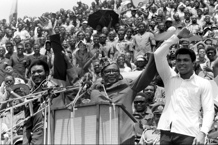 """FILE - Zaire's President Mobutu Sese Seko, center, raises the arms of heavyweight champion George Foreman, left, and Muhammad Ali, right, in Kinshasa, Zaire, Sept. 22, 1974. The two boxing greats faced off in the legendary """"Rumble in the Jungle"""" figh..."""