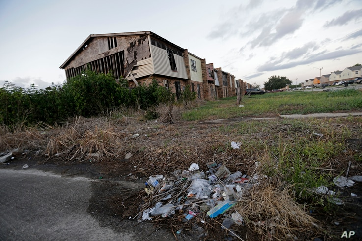 A pile of garbage sits in front of an abandoned section of an apartment complex which was destroyed in 2005 by Hurricane Katrina, in New Orleans, Louisina, Aug. 6, 2015.