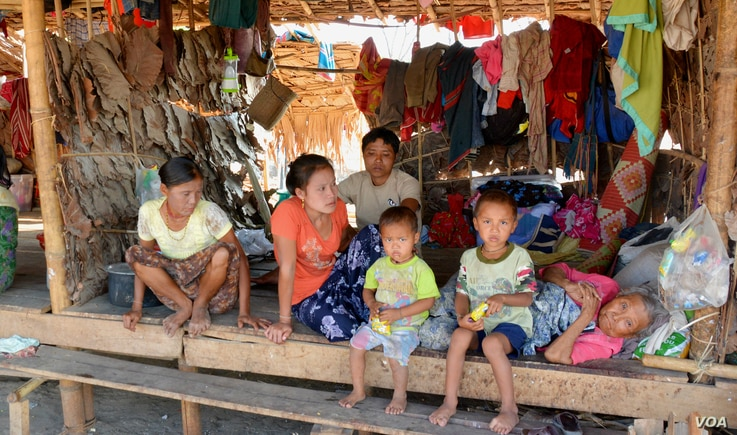 A displaced Kayin family sit in their unit of a shelter at Myaing Gyi Ngu camp, northern Kayin State. (P. Vrieze/VOA)