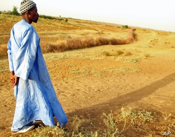 A farmer in Senegal walks across parched land which used to be a riverbed