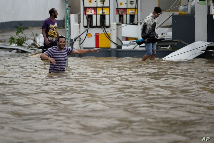 People walk next to a gas station flooded and damaged by the impact of Hurricane Maria, which hit the eastern region of the island, in Humacao, Puerto Rico, Sept. 20, 2017.