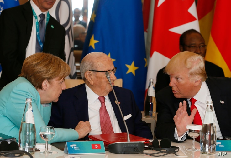 U.S. President Donald Trump and German Chancellor Angela Merkel speak with Tunisian President Beji Caid Essebsi as they attend a round table meeting of G-7 leaders and Outreach partners at the Hotel San Domenico in Taormina, Italy, May 27, 2017.