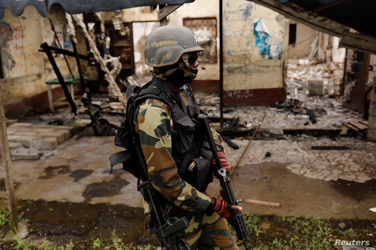 A Cameroonian elite Rapid Intervention Battalion (BIR) member patrols the abandoned village of Elona  near Buea in the anglophone southwest region, Cameroon, Oct. 4, 2018.