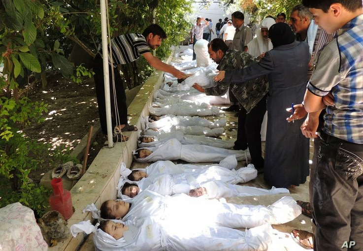 A citizen journalism image provided by the Local Committee of Arbeen which has been authenticated based on contents and AP reporting, shows Syrian citizens trying to identify dead bodies, after an alleged poison gas attack by government forces. There