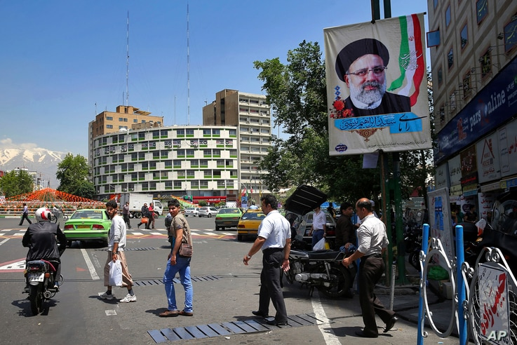 Pedestrians walk under an electoral banner of presidential candidate Ebraim Raisi in a square in downtown Tehran, Iran, Thursday, May 11, 2017.