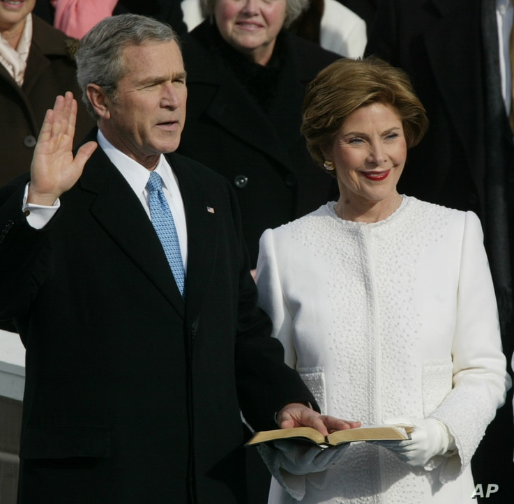 FILE - President Bush takes the oath of office with first lady Laura Bush at his side at the US Capitol in Washington, Jan. 20, 2005.