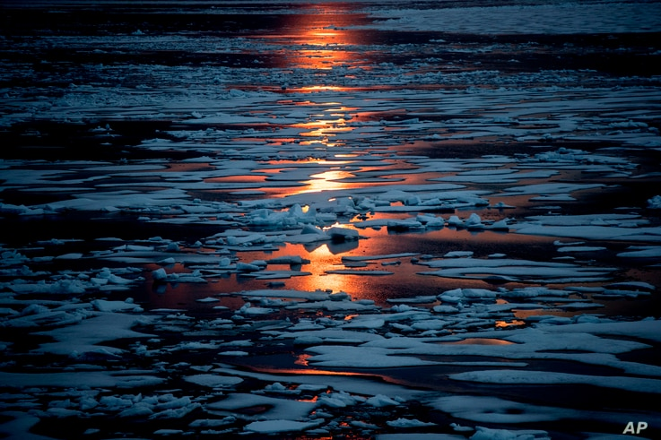 In this July 23, 2017, file photo the midnight sun shines across sea ice along the Northwest Passage in the Canadian Arctic Archipelago. The magnetic north pole is wandering about 34 miles (55 kilometers) a year.