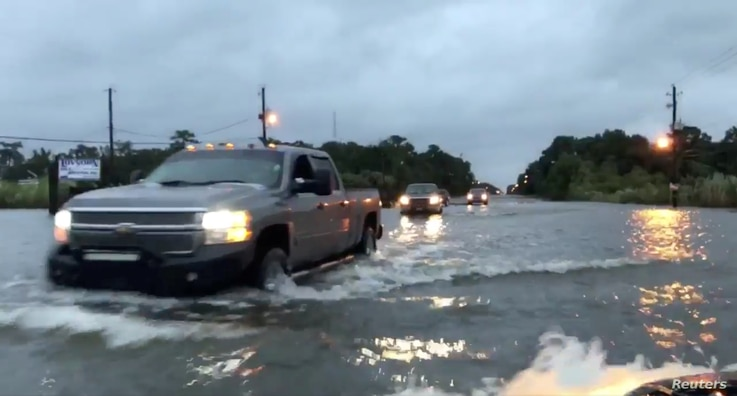 Cars drive through a flooded road in Mobile, Alabama, U.S., October 8, 2017, in this still image taken from a video obtained from social media. Michael Schubert/social media/via REUTERS