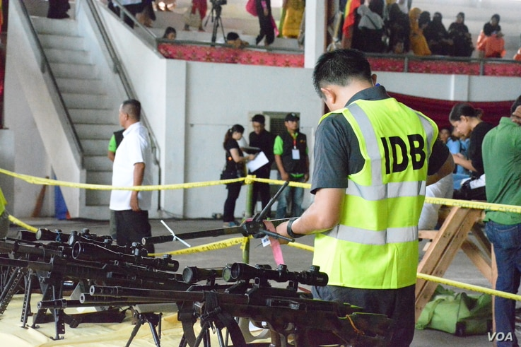A member of the Independent Decommissioning Body inspects and tags weapons turned over by Moro Islamic Liberation Fighters at a ceremonial laying down of arms in Sultan Kudarat, Maguindanao Province, the Philippines, June 16, 2015. (VOA/Simone Orenda...