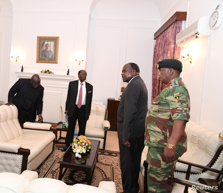 FILE - Zimbabwe's President Robert Mugabe meets with Father Fidelis Mukonori, Secretary to the Cabinet Dr Misheck Sibanda and Defense Forces Commander General Constantino Chiwenga at State House in Harare,  Nov. 19, 2017.