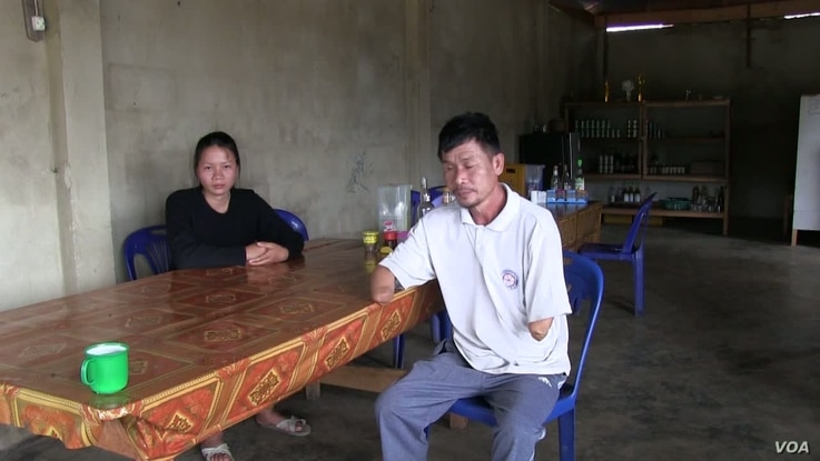 Houng Phomma Chak sits at a table with his daughter. In 2004, he lost both of his lower arms and was blinded in one eye when a bomb exploded while he was out collecting the old casings to sell for scrap metal.
