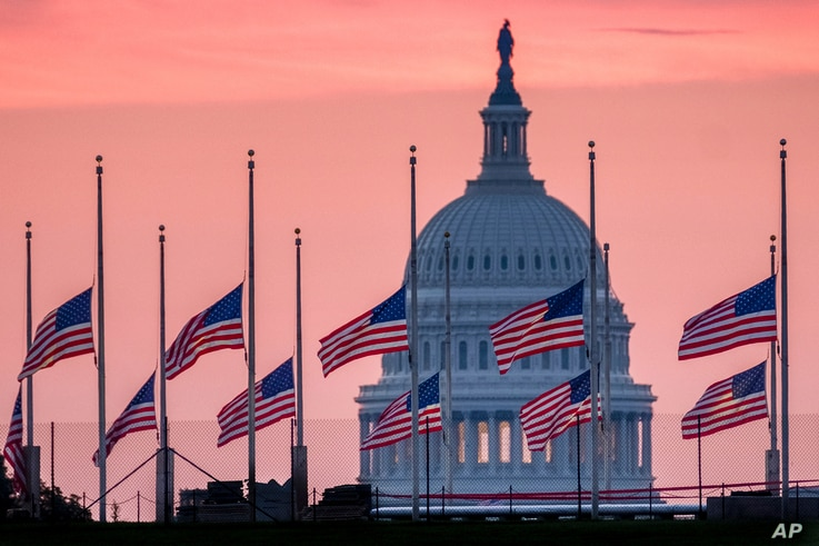 Flags flying a half-staff in honor of Sen. John McCain, R-Ariz., frame the U.S. Capital at daybreak in Washington,  Aug. 26, 2018.