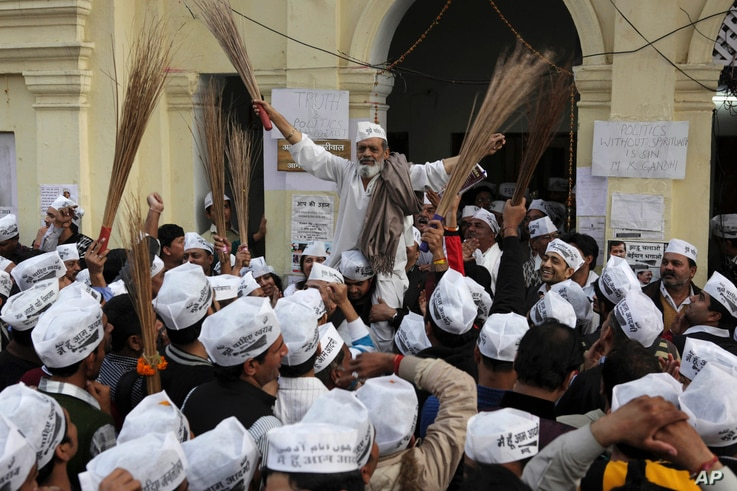 India's Aam Aadmi Party, or Common Man's Party, supporters with brooms, the party symbol, celebrate the party's performance in Delhi state Assembly elections, in New Delhi, Dec. 8, 2013.