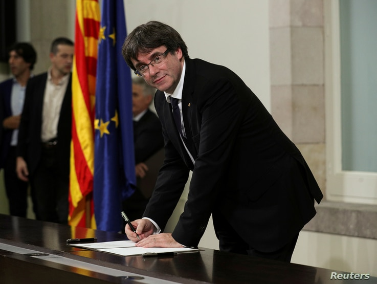 Catalan President Carles Puigdemont signs a declaration of independence at the Catalan regional parliament in Barcelona, Spain, Oct. 10, 2017.