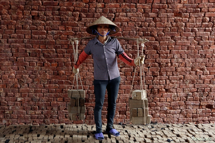 Phung Thi Hai, 54, carries bricks at a factory outside Hanoi, Vietnam, Feb. 27, 2017.