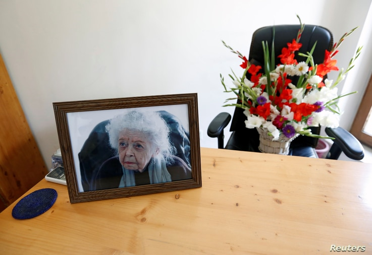 A photograph of late Nancy Hatch Dupree, an American historian, and a bouquet of flowers are seen in her office after she passed away, in Afghanistan Centre at Kabul University (ACKU), in Kabul, Afghanistan, Sept. 10, 2017.