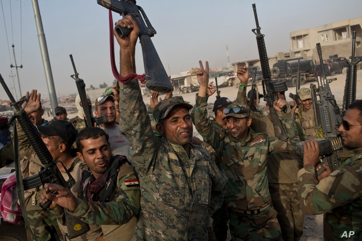 Iraqi army soldiers celebrate on the outskirts of Qayyarah, Iraq, Oct. 19, 2016. When troops arrived at a nearby village, they found the residents had risen up and killed Islamic State fighters.