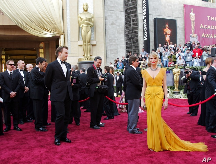 """Australian actor Heath Ledger, front left, nominated for an Oscar for best actor in a leading role for his work in """"Brokeback Mountain,"""" arrives with his girlfriend actress Michelle Williams, front right, a nominee for best supporting actress for her..."""