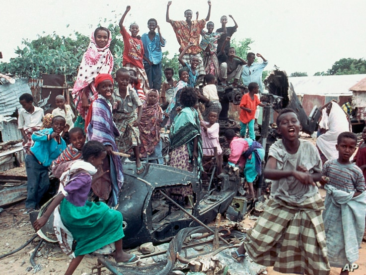 FILE - In this Oct. 19, 1993 photo, a group of young Somalis chant anti-American slogans while sitting atop the burned out hulk of a U.S. Black Hawk helicopter, shot down during a firefight with Somali guerrillas, in Mogadishu, Somalia.