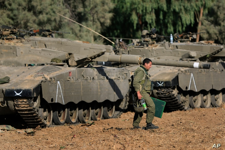 FILE - An Israeli soldier walks past tanks near the Israel and Gaza border, July 10, 2014. Israel is looking to boost the amount of money the United States sends it every year for military aid to as much as $5 billion.