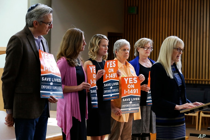 FILE - Marilyn Balcerak, right, of Bonney Lake, Wash., speaks at a news conference in Bellevue, Wash., in support of Initiative 1491, which would allow family members and law enforcement officials to petition a judge to temporarily suspend a person'...