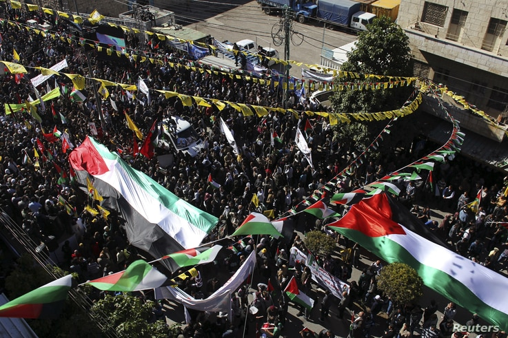 People carry large Palestinian flags during a rally in the West Bank city of Hebron, November 29, 2012.