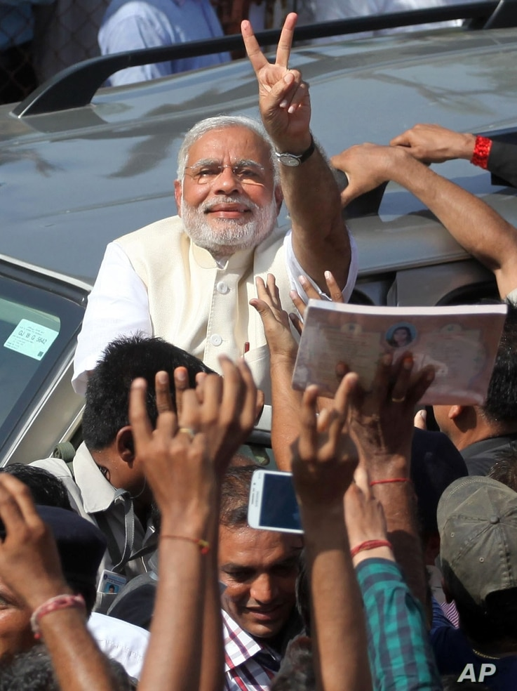 India's main opposition Bharatiya Janata Party's prime ministerial candidate Narendra Modi displays the victory symbol to supporters after casting his vote in Ahmadabad, India, April 30, 2014.