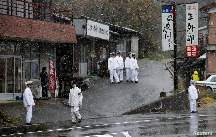 Police officers stand guard before Russia's President Vladimir Putin leaves a hot spring resort, the venue of the summit meeting between Japanese Prime Minister Shinzo Abe and Putin, Dec. 15, 2016, during snow falling in Nagato, Yamaguchi prefecture...