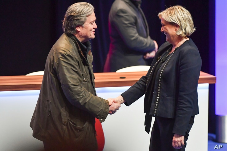 FILE - National Front party leader Marine Le Pen (R) greets on stage former White House strategist Steve Bannon at the party congress in the northern French city of Lille, March 10, 2018.