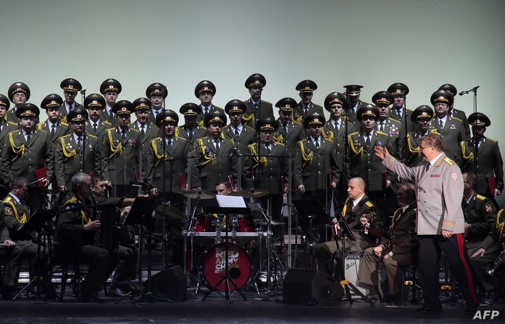 FILE - This photo taken on Oct. 23, 2015 shows the official army choir of the Russian armed forces, also known as the Alexandrov Ensemble, standing while the choir Conductor General Viktor Eliseev (R) arrives onstage at the Palais des Sports in Paris...