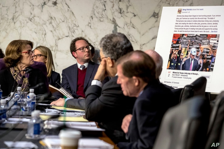 Democratic Sen. Dianne Feinstein, left, looks at a poster depicting an example of a misleading internet ad as representatives of Facebook, Twitter and Google testify during hearing on Capitol Hill in Washington, Oct. 31, 2017.