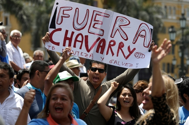 "A demonstrator holds up a poster that reads in Spanish: ""Get out Chavarry!"", referring to Attorney General Pedro Chavarry, in Lima, Peru, Jan. 2, 2019."