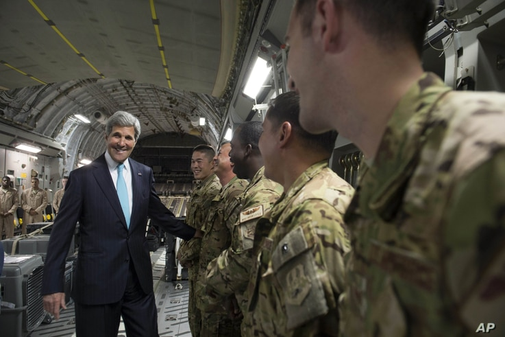 U.S. Secretary of State John Kerry, left, talks with the crew of a U.S. Air Force C-17 military airplane prior to departure from Addis Ababa, Ethiopia, enroute to Juba, South Sudan, Friday, May 2, 2014. Kerry is urging South Sudan's warring governmen