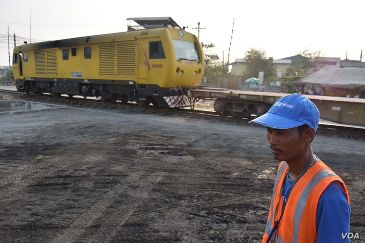 A worker looks on as Cambodia's sole trainline is loaded with cargo destined for the counrty's largest seaport in Sihanoukville. (D. de Carteret for VOA)