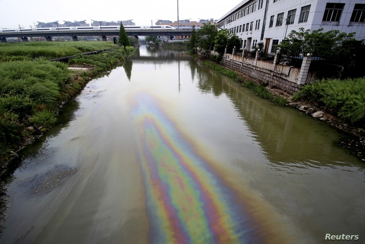 FILE - A China Railway High-speed (CRH) Harmony bullet train travels above a river polluted by leaked fuel, in Shaoxing, Zhejiang province, China on April 29, 2015.