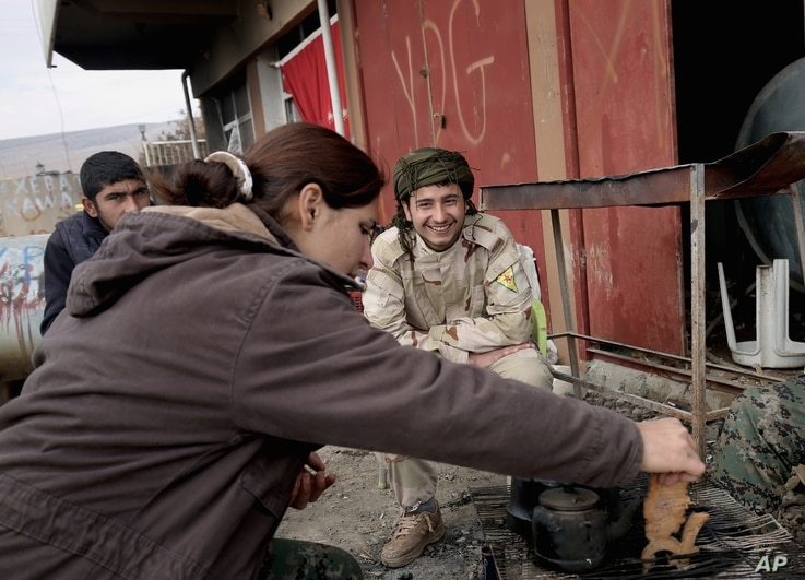 FILE - A fighter from the Syria-based People's Protection Units (YPG) smiles at a female fighter from the Turkey-based Kurdish Workers' Party at their base while they sit around a fire on the outskirts of the town of Sinjar, northern Iraq, on Jan. 29...