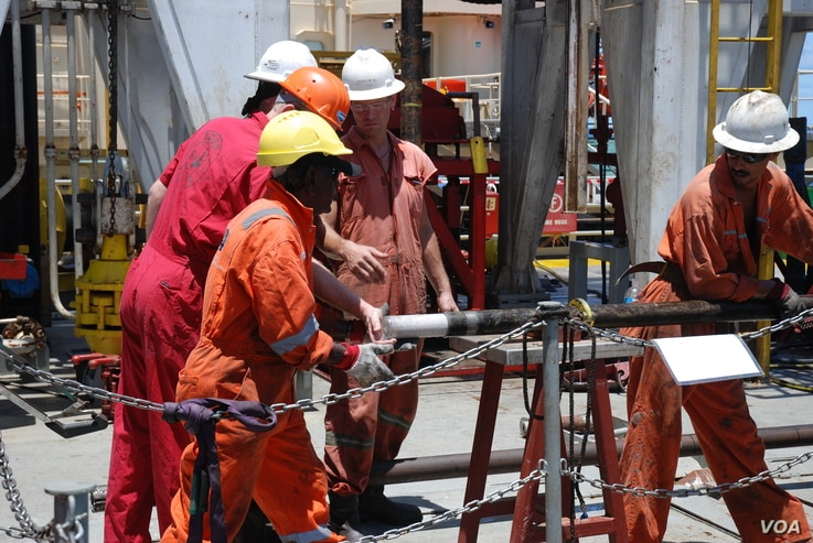 A core containing fossil coral material is removed from the core barrel aboard the Greatship Maya. (Credit: G. Lott, ECORD/IODP)