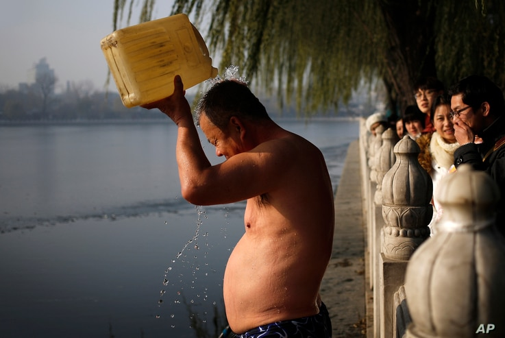 FILE - People in winter clothes watch a Chinese man pouring icy water on himself as he prepares to swim in the half-iced water at Shichahai Lake in Beijing on Nov. 29, 2015.