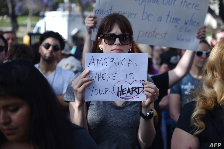 "Critics of U.S. government policy which separates children their parents when they cross the border illegally from Mexico protest during a ""Families Belong Together March,"" in downtown Los Angeles, California, June 14, 2018."