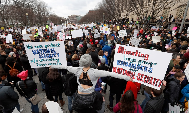 Protesters carry signs and chant on Pennsylvania Avenue near the White House during a demonstration to denounce President Donald Trump's executive order that bars citizens of seven predominantly Muslim-majority countries from entering the U.S. on Sun...