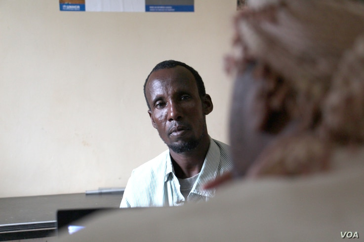 Ibrahim Hussein, a father of seven, is taken through the repatriation by an UNHCR representative, Dadaab, Kenya, April 27, 2015. (Mohammed Yusuf/VOA).