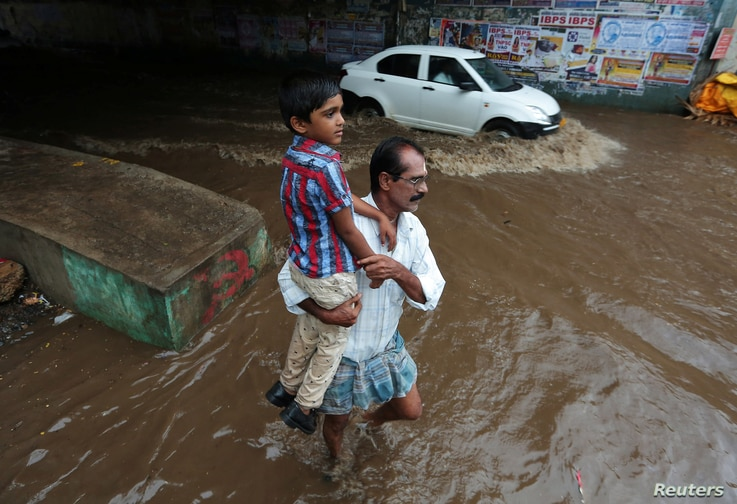 A man carries a child as he wades through a waterlogged subway after heavy rains in Chennai, India, Aug. 9, 2017.