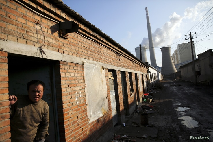 FILE - A migrant worker steps out of his  living quarters in an area next to a coal power plant in Beijing.