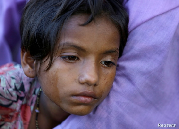An exhausted Rohingya refugee girl leans on a family member after crossing the Bangladesh-Myanmar border while being detained by the Border Guard Bangladesh near Inani beach in Cox's Bazar, Bangladesh, Nov. 7, 2017.
