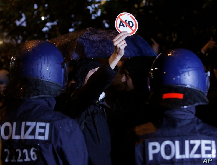 Police blocks demonstrators protesting against the nationalist Alternative for Germany, AfD, party in Berlin, Germany, Sept. 24, 2017.