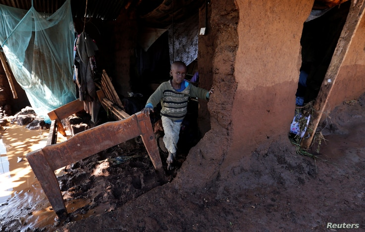 A child walks in his house, which was partly destroyed by flooding water after a dam burst, in Solio town near Nakuru, Kenya May 10, 2018.