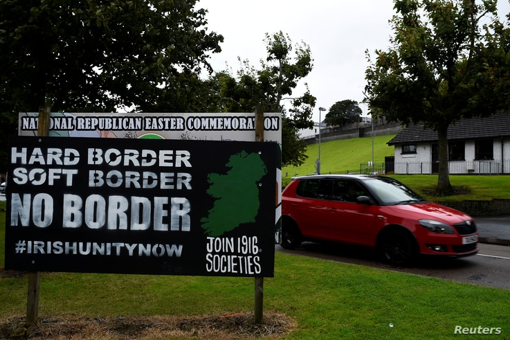 "FILE PHOTO: A car drives past a sign saying ""No Border, Hard border, soft border, no border"" in Londonderry, Northern Ireland, Aug. 16, 2017."