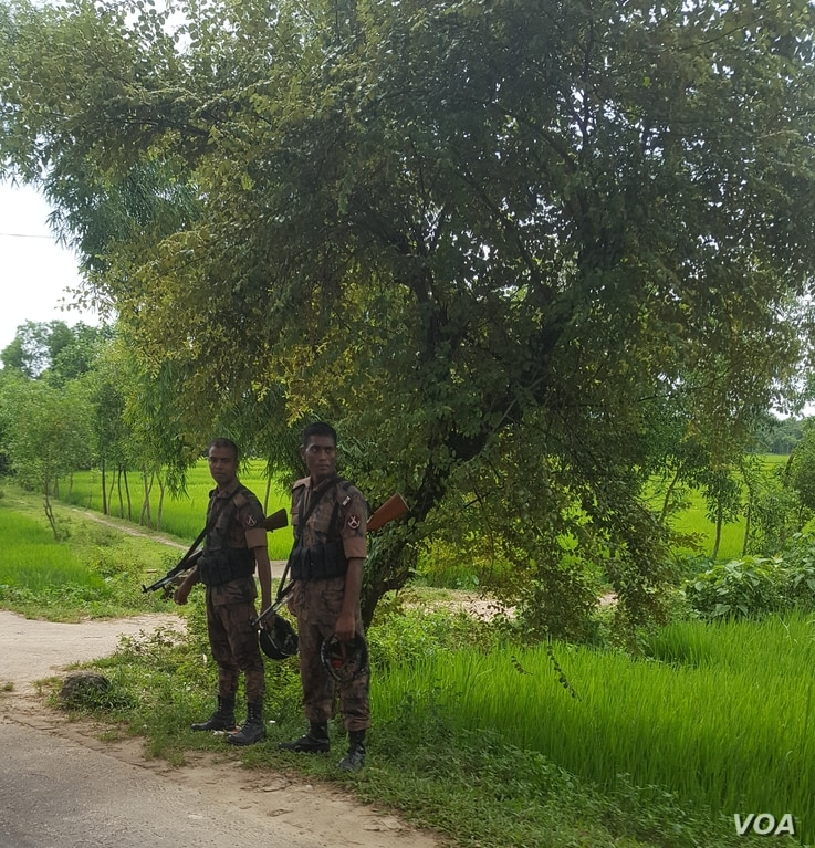 Bangladeshi soldiers stand beside the road leading to Kutupalong refugee camp in Bangladesh, Oct. 6, 2017.